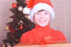 Muchacho sonriente del niño que lleva el sombrero de santa sobre luces de la Navidad Fotos de archivo libres de regalías