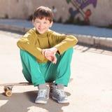Muchacho sonriente del niño que se sienta en el monopatín al aire libre Fotos de archivo
