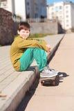Muchacho sonriente del niño que se sienta en el monopatín al aire libre Foto de archivo libre de regalías