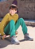 Muchacho sonriente del niño que se sienta en el monopatín al aire libre Imagen de archivo libre de regalías