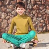 Muchacho sonriente del niño que se sienta en el monopatín al aire libre Fotografía de archivo