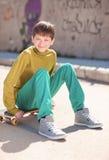 Muchacho sonriente del niño que se sienta en el monopatín al aire libre Fotografía de archivo libre de regalías