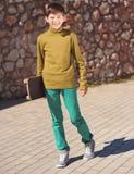 Muchacho sonriente del niño que sostiene el monopatín al aire libre Fotos de archivo