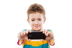 Muchacho sonriente del niño que sostiene el teléfono móvil o smartphone que toma a uno mismo Imagenes de archivo