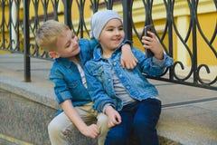 Muchacho sonriente del niño que toma el selfie al aire libre Niñez Fotos de archivo