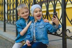Muchacho sonriente del niño que toma el selfie al aire libre Niñez Foto de archivo libre de regalías