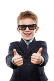 Muchacho sonriente del niño en gesticular de las gafas de sol del traje de negocios que lleva Foto de archivo libre de regalías
