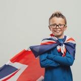 Muchacho sonriente del super héroe con el cabo británico de la bandera fotos de archivo libres de regalías