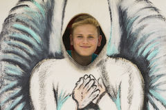 Muchacho sonriente detrás de la pintura del ángel Fotos de archivo