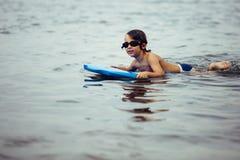 Muchacho sonriente en bodyboard en agua fotografía de archivo