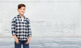 Muchacho sonriente en camisa a cuadros y vaqueros Foto de archivo libre de regalías