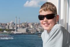 Muchacho sonriente en gafas de sol contra un paisaje Foto de archivo