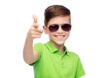 Muchacho sonriente en gafas de sol y camiseta verde del polo Imagen de archivo libre de regalías