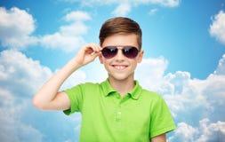 Muchacho sonriente en gafas de sol y camiseta verde del polo Fotos de archivo