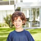 Muchacho sonriente en jardín Foto de archivo
