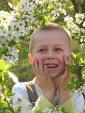 Muchacho sonriente en jardín floreciente imagen de archivo libre de regalías