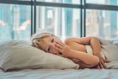Muchacho sonriente en la cama que despierta en una ciudad grande en el fondo de Imágenes de archivo libres de regalías