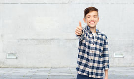 Muchacho sonriente en la camisa a cuadros que muestra los pulgares para arriba Foto de archivo libre de regalías
