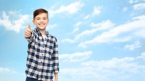 Muchacho sonriente en la camisa a cuadros que muestra los pulgares para arriba Imagenes de archivo