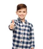 Muchacho sonriente en la camisa a cuadros que muestra los pulgares para arriba Fotos de archivo