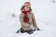 Muchacho sonriente en la ropa caliente que se sienta en nieve Fotografía de archivo libre de regalías
