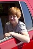 Muchacho sonriente en la ventana del coche Fotografía de archivo