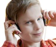 Muchacho sonriente en música que escucha de los auriculares. Aislado en blanco. Foto de archivo libre de regalías