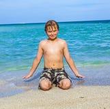 Muchacho sonriente en una playa tropical Imágenes de archivo libres de regalías
