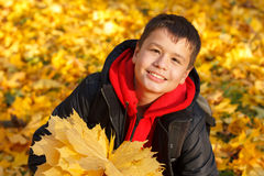 Muchacho sonriente feliz con las hojas de otoño Fotos de archivo