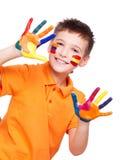 Muchacho sonriente feliz con manos y cara pintadas. Imagen de archivo