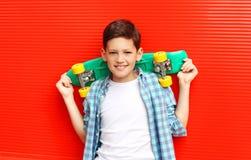 Muchacho sonriente feliz del adolescente del retrato que lleva un monopatín a cuadros del shirtwith en ciudad Imagen de archivo