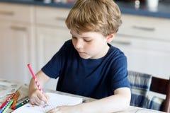 Muchacho sonriente feliz del niño en casa que hace letras de la escritura de la preparación con las plumas coloridas Foto de archivo libre de regalías