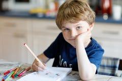 Muchacho sonriente feliz del niño en casa que hace letras de la escritura de la preparación con las plumas coloridas Imagenes de archivo