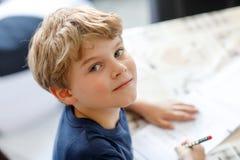 Muchacho sonriente feliz del niño en casa que hace letras de la escritura de la preparación con las plumas coloridas Fotografía de archivo libre de regalías