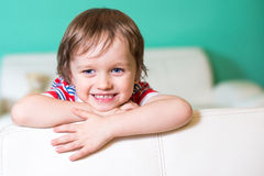 Muchacho sonriente feliz del pequeño niño que se sienta en un sofá fotos de archivo