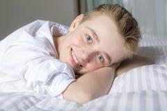 Muchacho sonriente feliz que miente en cama en casa Imágenes de archivo libres de regalías