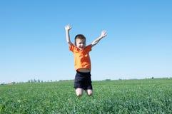 Muchacho sonriente feliz que salta la hierba alta, verde y el cielo azul en el fondo, el éxito, la fortuna, el logro y ganar fotografía de archivo libre de regalías
