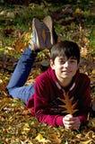 Muchacho sonriente feliz que sostiene la hoja del otoño Imagen de archivo libre de regalías