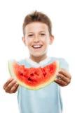 Muchacho sonriente hermoso del niño que lleva a cabo la rebanada roja de la fruta de la sandía Fotos de archivo