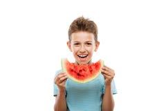 Muchacho sonriente hermoso del niño que lleva a cabo la rebanada roja de la fruta de la sandía Fotografía de archivo libre de regalías