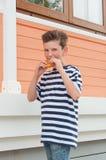 Muchacho sonriente joven con un peinado de moda y una hamburguesa Foto de archivo libre de regalías