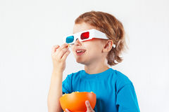 Muchacho sonriente joven en los vidrios 3D que come las palomitas Imágenes de archivo libres de regalías