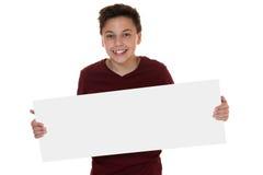 Muchacho sonriente joven que lleva a cabo una muestra vacía con el copyspace Foto de archivo libre de regalías