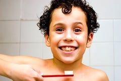 Muchacho sonriente lindo con el cepillo de dientes imagen de archivo libre de regalías