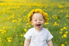 Muchacho sonriente lindo en guirnalda del diente de león en el campo de la primavera Imagen de archivo