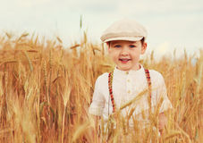 Muchacho sonriente lindo que camina el campo de trigo Imagenes de archivo