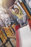 Muchacho sonriente lindo que juega en diapositiva en parque imagenes de archivo