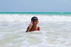 Muchacho sonriente lindo que se divierte que juega con la agua de mar Imagen de archivo libre de regalías