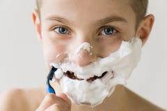 Muchacho sonriente que afeita la cara con la maquinilla de afeitar plástica Fotos de archivo libres de regalías
