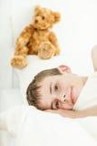 Muchacho sonriente que coloca cerca de oso de la felpa Imagenes de archivo